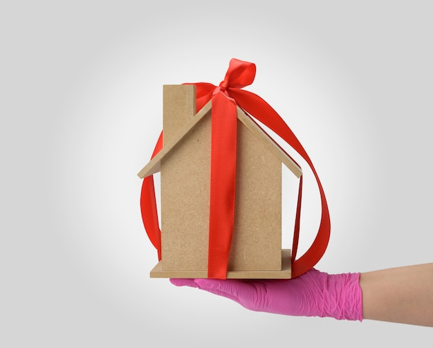 Kobiece ręce trzymają model drewnianego domu przewiązanego czerwoną jedwabną wstążką, pojęcie zakupu nieruchomości, hipoteka