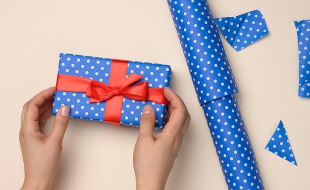 Kobiece ręce trzymają niebieskie pudełko na beżowym tle, koncepcja gratulacji z okazji urodzin, święta