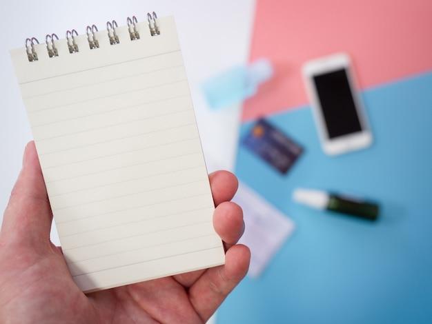 Kobiece ręce trzymają notatnik ze smartfonem, maską chirurgiczną, kartą kredytową i środkiem dezynfekującym w żelu alkoholowym