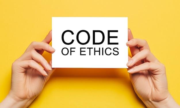 Kobiece ręce trzymają papier kartkowy z tekstem kodeksu etyki na żółtym polu