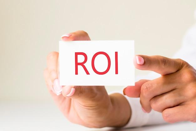 Kobiece ręce trzymają papier kartkowy z tekstem roi - zwrot z inwestycji - na białym jasnym tle. koncepcja biznesu i finansów