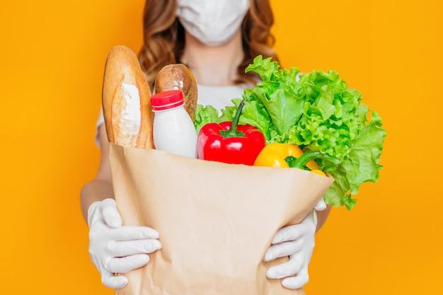 Kobiece ręce trzymają papierową torbę z produktami, warzywami, ziołami na białym tle nad pomarańczową ścianą, kwarantanną, koronawirusem, bezpieczną dostawą żywności, koncepcją pobytu w domu