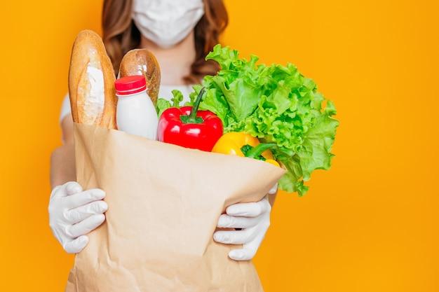 Kobiece ręce trzymają papierową torbę z produktami, warzywami, ziołami na białym tle nad pomarańczową ścianą, kwarantanną, koronawirusem, bezpieczną dostawą żywności, miejsca na kopię