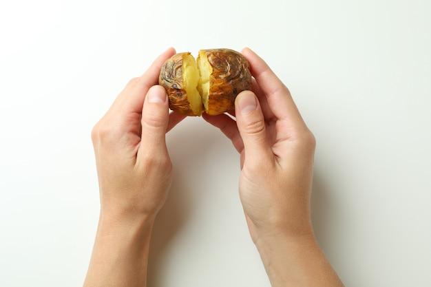 Kobiece ręce trzymają pieczonego ziemniaka na białym tle.