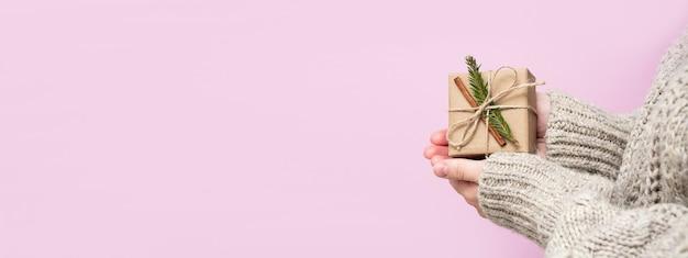 Kobiece ręce trzymają prezent z gałązką choinki i cynamonem na różowym tle, zbliżenie, kopia przestrzeń. koncepcja ręcznie robione prezenty. boże narodzenie, nowy rok, tło z miejscem na tekst, baner.