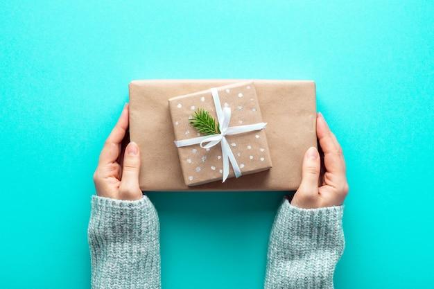 Kobiece ręce trzymają prezenty świąteczne w ekologicznym papierze do pakowania na lazurze