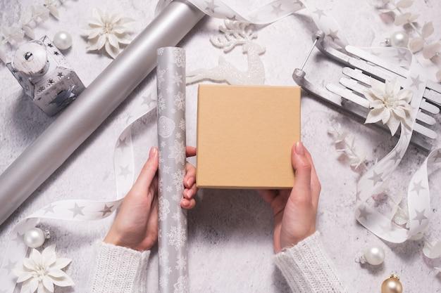Kobiece ręce trzymają pudełko do pakowania w kolorze srebrnym i białym na boże narodzenie. makieta