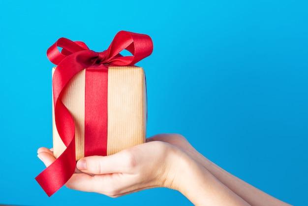 Kobiece ręce trzymają pudełko z czerwoną kokardą na niebiesko