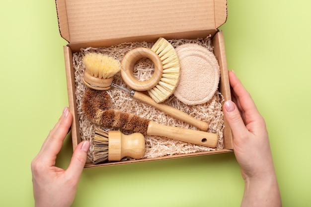 Kobiece ręce trzymają pudełko z przyjaznymi dla środowiska narzędziami do czyszczenia