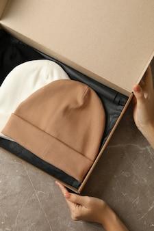 Kobiece ręce trzymają pudełko z różnymi czapkami na szarym stole