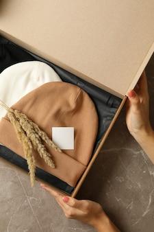 Kobiece ręce trzymają pudełko z różnymi czapkami