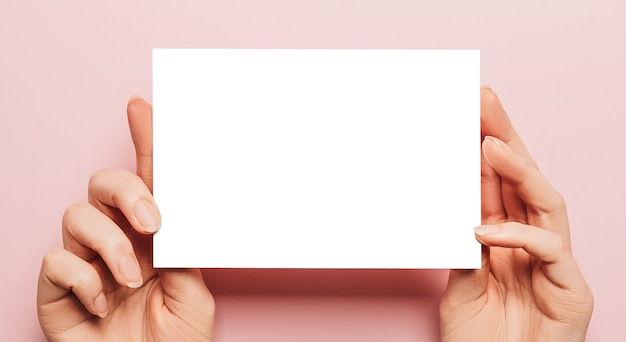 Kobiece ręce trzymają pustą kartkę papieru na różowym tle. przestrzeń reklamowa