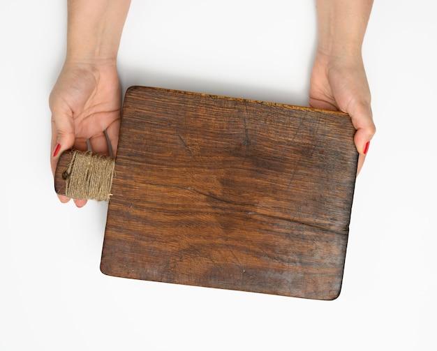 Kobiece ręce trzymają pustą prostokątną brązową drewnianą deskę do krojenia na białym tle