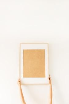 Kobiece ręce trzymają pustą ramkę na zdjęcia z pustą makietą miejsca