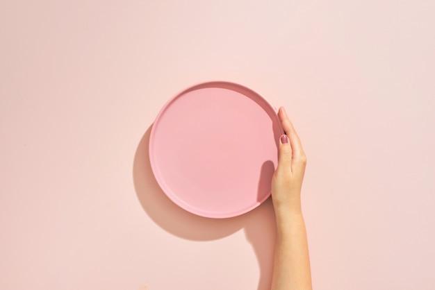 Kobiece ręce trzymają puste różowe naczynie na różowym stole