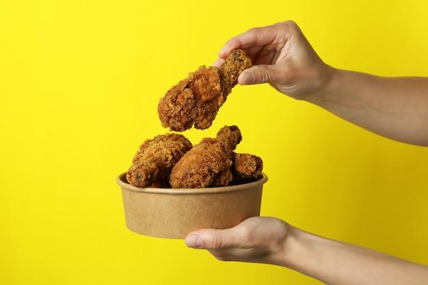 Kobiece ręce trzymają smażonego kurczaka na żółtym tle