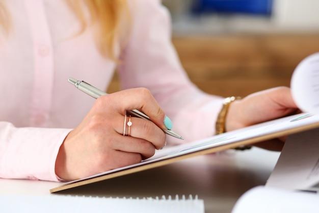 Kobiece ręce trzymają srebrny długopis i podkładkę