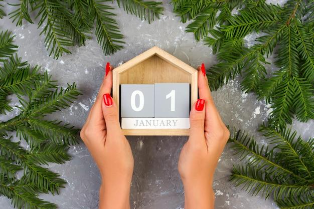 Kobiece ręce trzymają świąteczny kalendarz, 1 stycznia na szarym cementowym stole z dekoracją