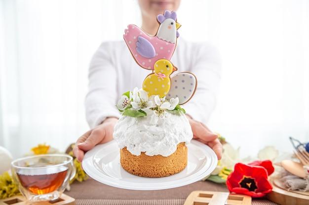 Kobiece ręce trzymają świąteczny tort wielkanocny, ozdobiony kwiatami i jasnymi detalami.