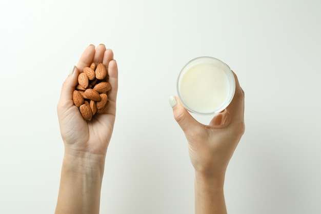 Kobiece ręce trzymają szklankę mleka i migdałów na białym tle, widok z góry