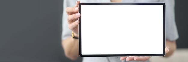 Kobiece ręce trzymają tablet z białym ekranem do nauki online