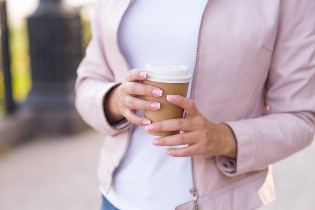 Kobiece ręce trzymają tekturowy kubek z aromatyczną kawą na ulicy