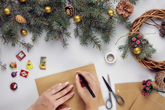 Kobiece ręce trzymają wesołą kartkę bożonarodzeniową i kopertę świąteczną dekorację tło płaskie świecki widok z góry