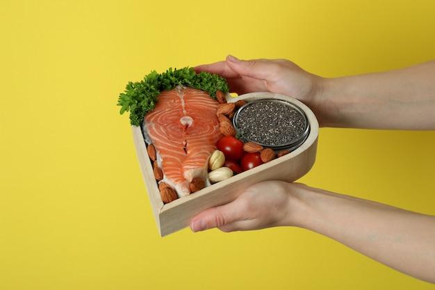 Kobiece ręce trzymają zdrową żywność na żółtym tle