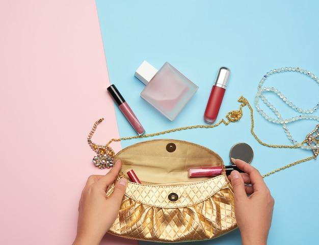 Kobiece ręce trzymają złotą kopertówkę z różnymi kosmetykami i biżuterią na niebieskim tle