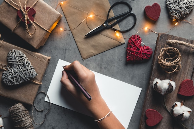 Kobiece ręce trzymając bonu upominkowego i pudełko. dziewczyna podpisuje pocztówkę na walentynki. prezent, romans, niespodzianka