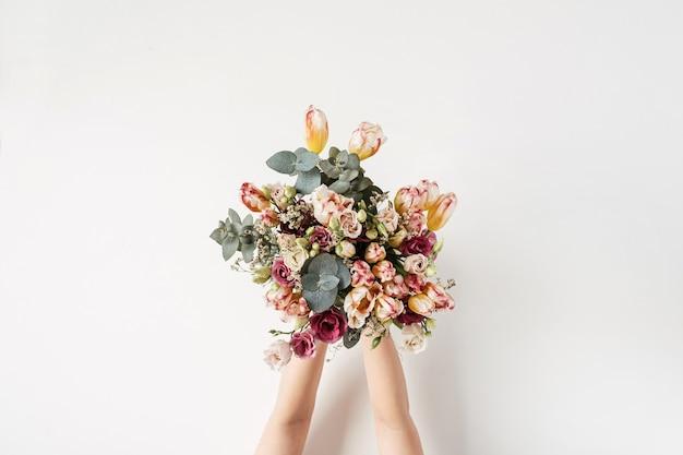 Kobiece ręce trzymając bukiet kwiatów na białej ścianie