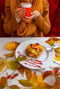 Kobiece ręce trzymając czerwony kubek kawa ciasto jesienne liście