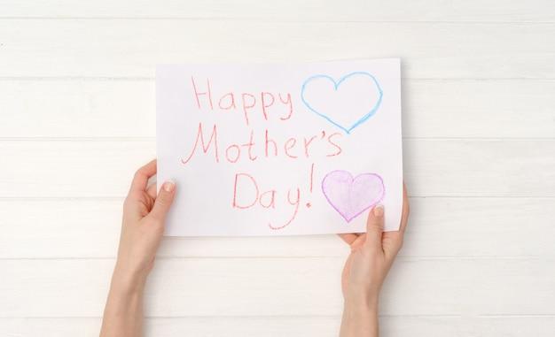 Kobiece ręce trzymając diy malowane pocztówka na dzień matki. koncepcja dzień szczęśliwej matki. widok z góry