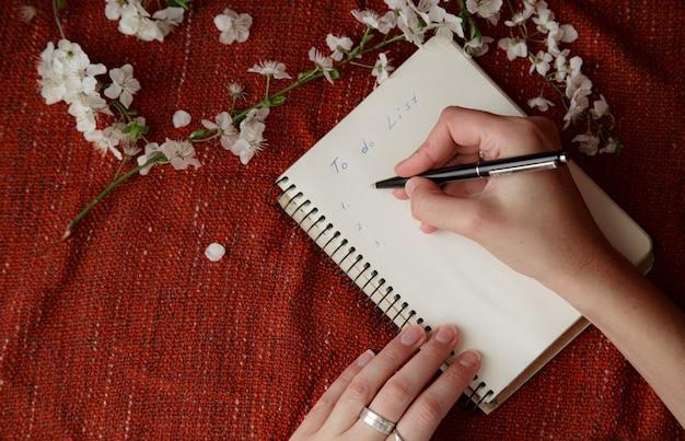Kobiece ręce trzymając długopis i notatnik spirala jako makieta dla swojego projektu. czerwone tło, płaski styl świeckich. pomysł i koncepcja wiosny, zmiany, życzenia i wyznaczania celów
