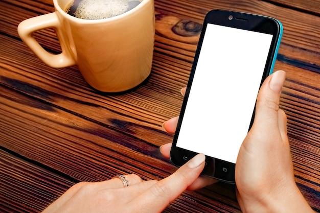 Kobiece ręce trzymając filiżankę kawy na drewnianym stole