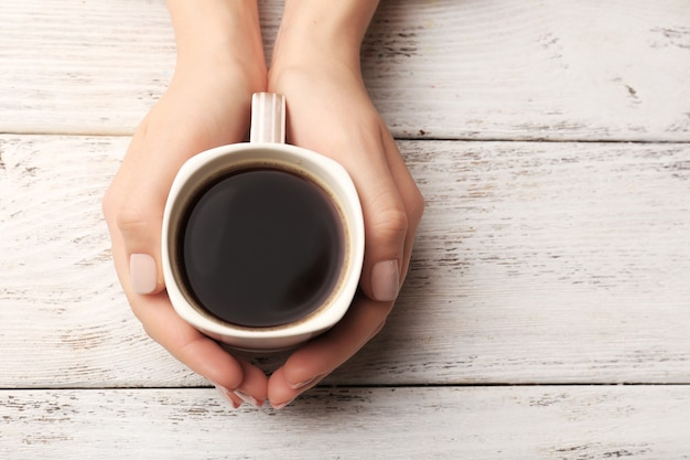 Kobiece ręce trzymając filiżankę kawy na drewnianym