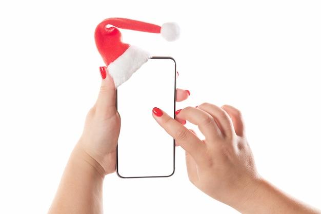 Kobiece ręce trzymając inteligentny telefon komórkowy z santa hat