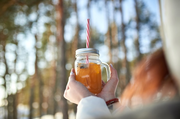 Kobiece ręce trzymając kieliszek grzanego wina na zimowy las