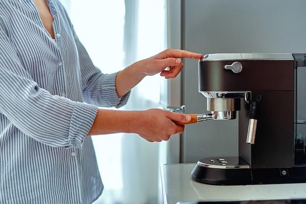 Kobiece ręce trzymając kolbę i robiąc świeżą aromatyczną kawę w domu przy użyciu nowoczesnego ekspresu do kawy