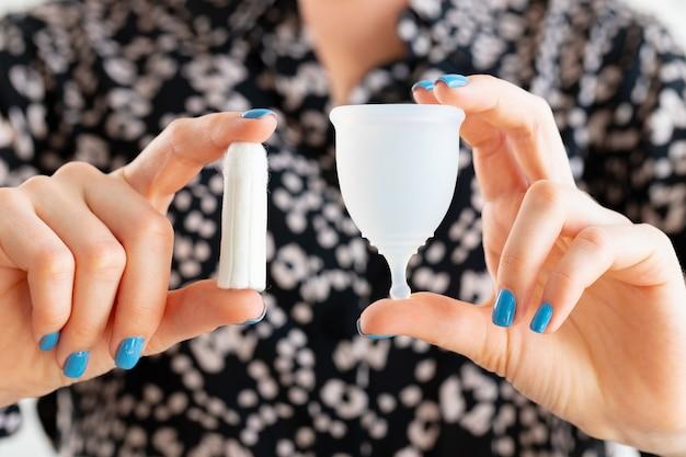 Kobiece ręce trzymając kubek menstruacyjny i tampon medyczny