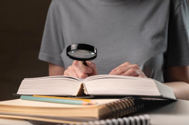 Kobiece ręce trzymając lupę i książki lub podręcznik, szukając informacji