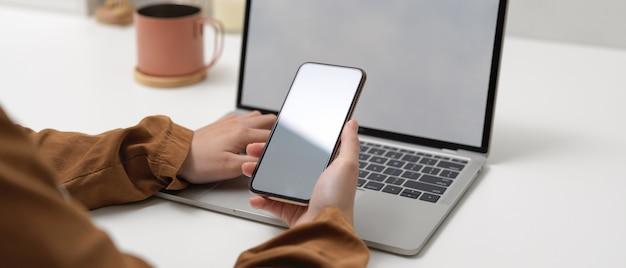 Kobiece ręce trzymając makiety smartfona siedząc przy stole roboczym z makiety laptopa w biurze domowym