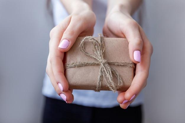 Kobiece ręce trzymając małe pudełko owinięte papierem rzemieślniczym ze wstążką. mały prezent na boże narodzenie lub nowy rok w rękach kobiety. boże narodzenie urodziny walentynki celebracja przedstawia romantyczną koncepcję