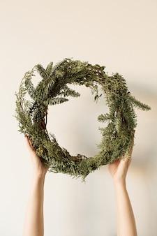 Kobiece ręce trzymając okrągłą ramę wieniec z gałęzi jodły i eukaliptusa na neutralnym.
