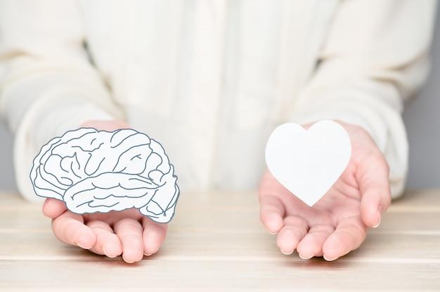Kobiece ręce trzymając papier wyciąć mózg i duszę. konflikt między emocjami a racjonalnym myśleniem. równowaga i równowaga między pojęciem umysłu i serca.