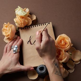 Kobiece ręce trzymając pióro i puste kartki papieru z kwiatami na brązowym stole, lato, leżał płasko