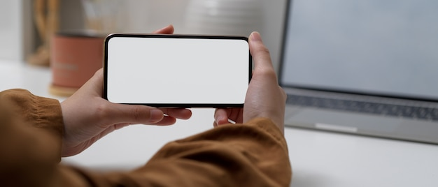 Kobiece ręce trzymając poziomą makietę smartfona siedząc przy stole roboczym z makietą laptopa