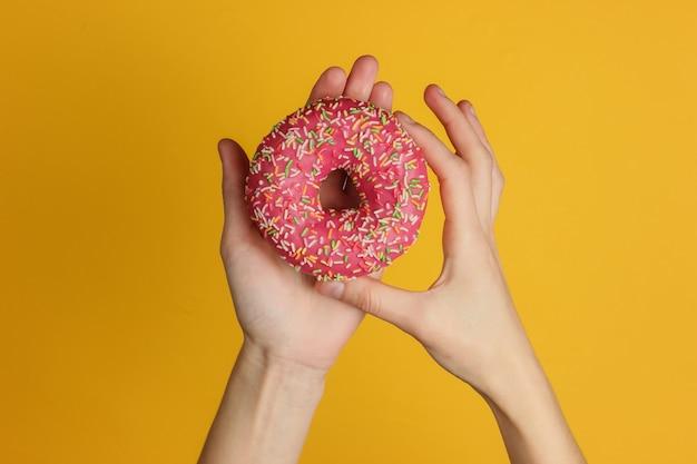 Kobiece ręce trzymając przeszklone pączek na żółtym tle. słodki deser. widok z góry.