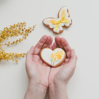Kobiece ręce trzymając przeszklone pierniki na białym tle. wiosna, koncepcja wesołych świąt. widok z góry