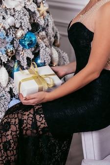 Kobiece ręce trzymając pudełko ozdobione złotą wstążką, na tle choinki